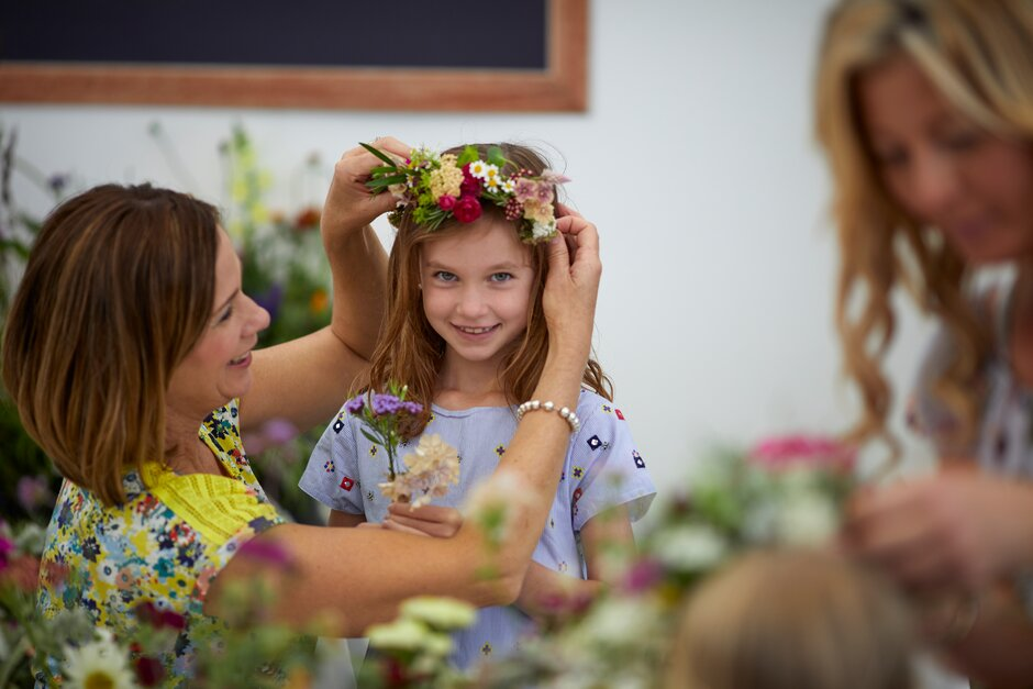 A mother and child in a flower crown workshop