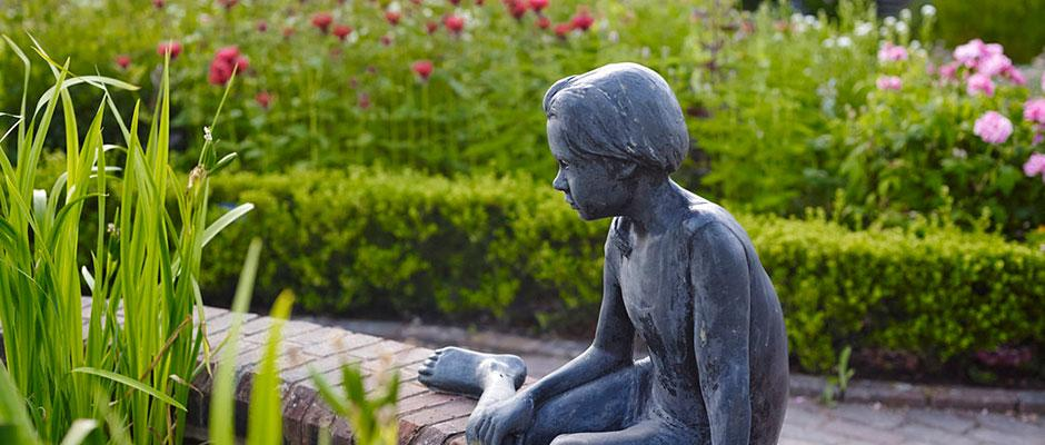 Statue of child on pond edge
