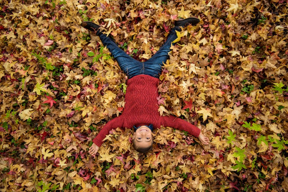 Girl reaching for autumn leaves
