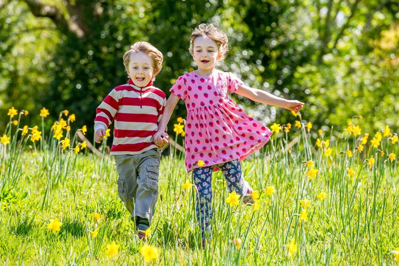 Boy and girl running in daffodils