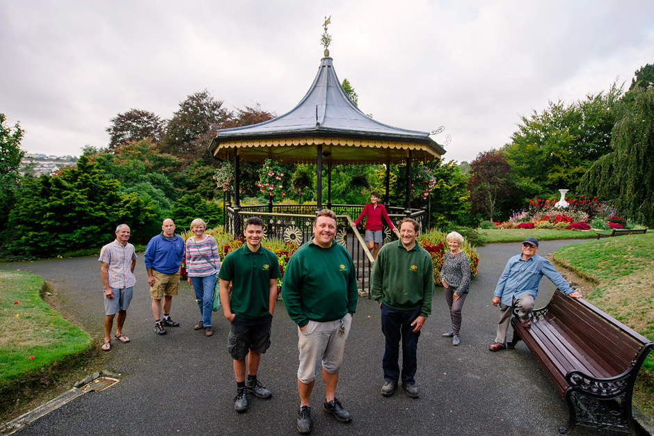 A group of gardeners pose for the camera in front of a bandstand in a public park