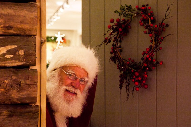 Father Christmas at a door with Christmas wreath