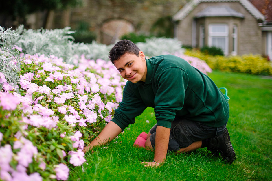A gardener smiles at the camera while kneeling to tend to pink flowers
