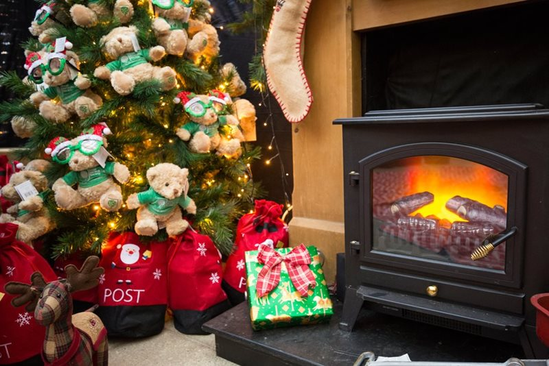Christmas teddies on a tree by the fire