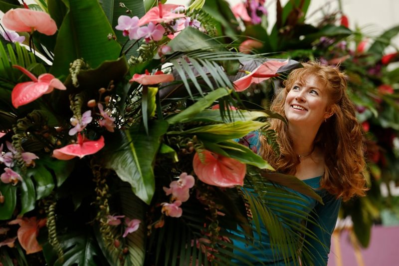 Visitor poses with phalenopsis
