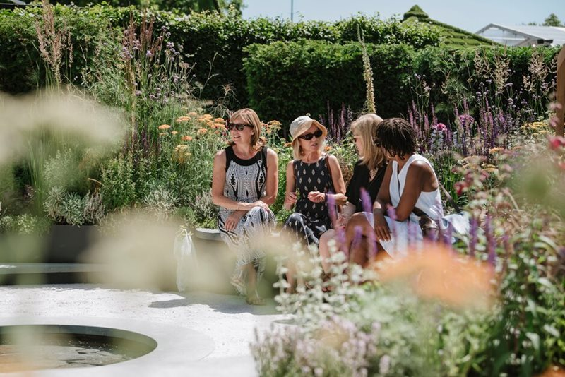 Visitors relax in a garden at Hampton Court Palace Garden Festival