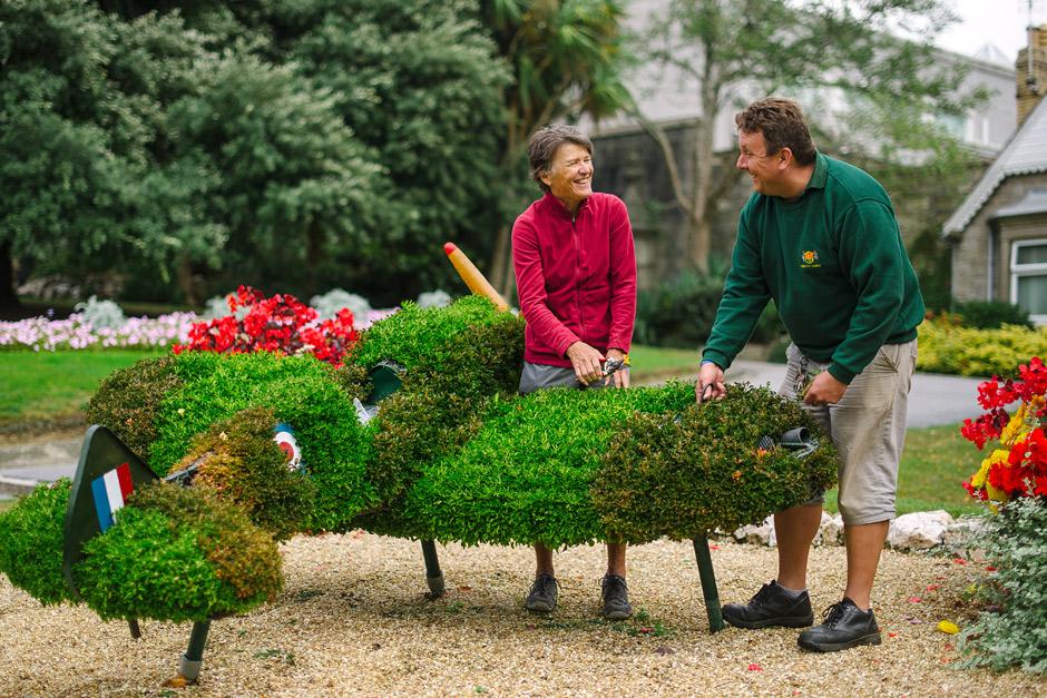 A man and woman share a joke while pruning an ornamental bush