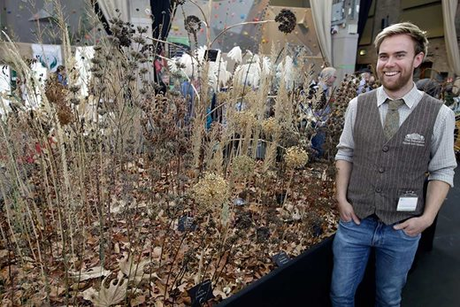 an exhibitor with a display of seedheads at the show