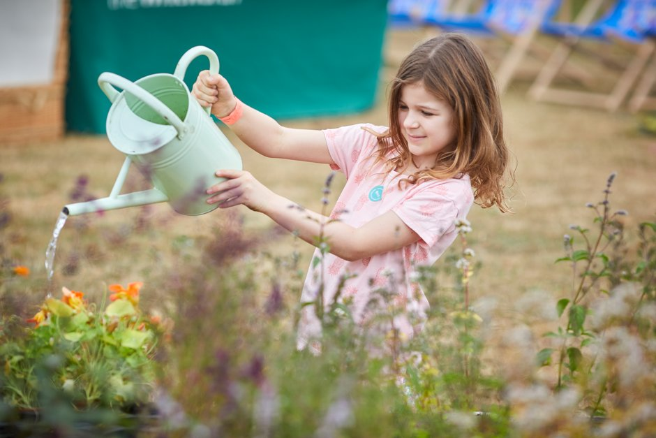 A girl helps to water plants