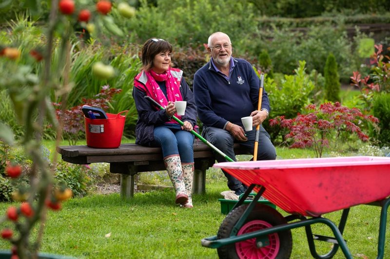 Volunteers sit down after work in a walled Community Garden, Castlecaulfield, Co Tyrone