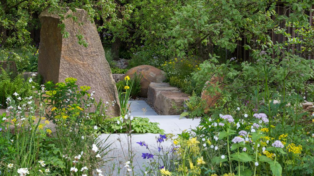 Woodland-edge planting and large rocks lead to a smoother path