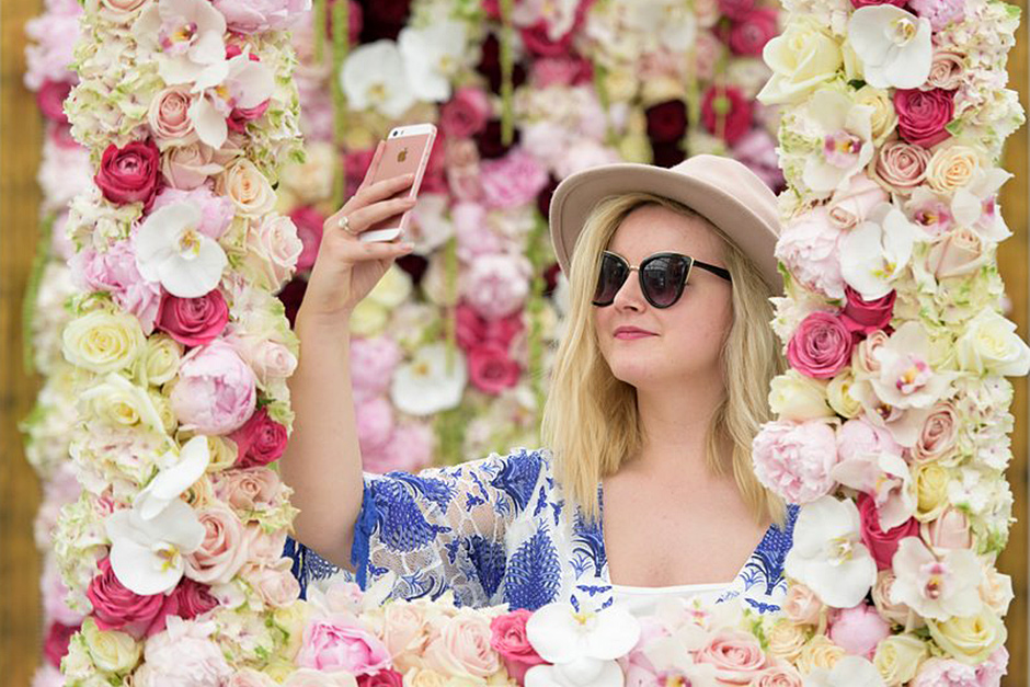 a visitor taking a selfie at a floral installation at the show