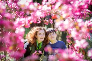 Woman and boy look at blossom at RHS Rosemoor
